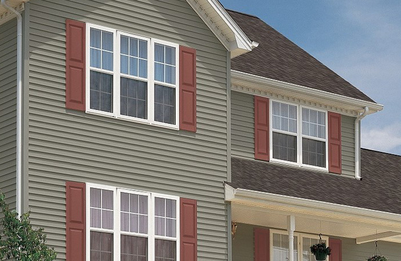 Green vinyl siding with burnt red shutters