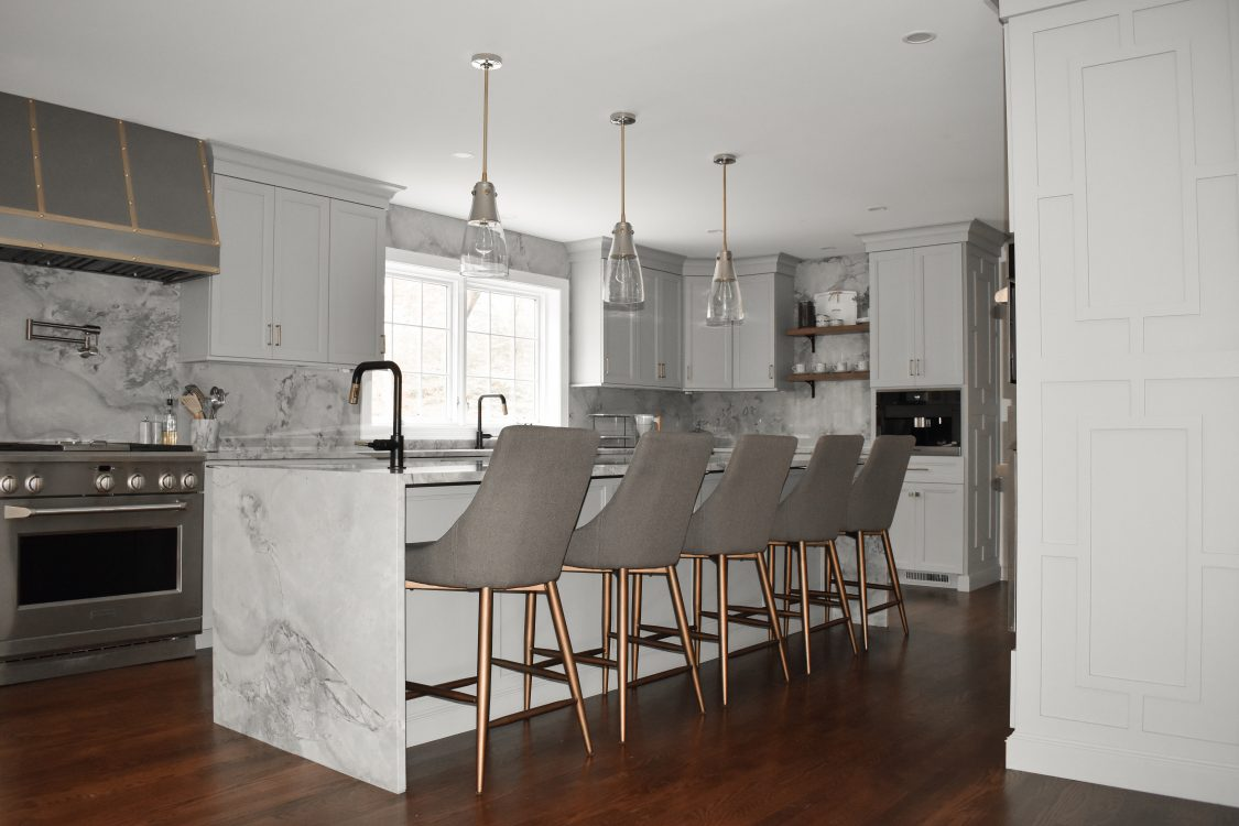 A modern kitchen in with white cabinets and matching marble walls and countertops